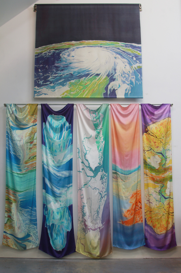 """Hurricane Katrina"" batik on silk, hanging on a decorative curtain rod in the studio with silk scarves below"